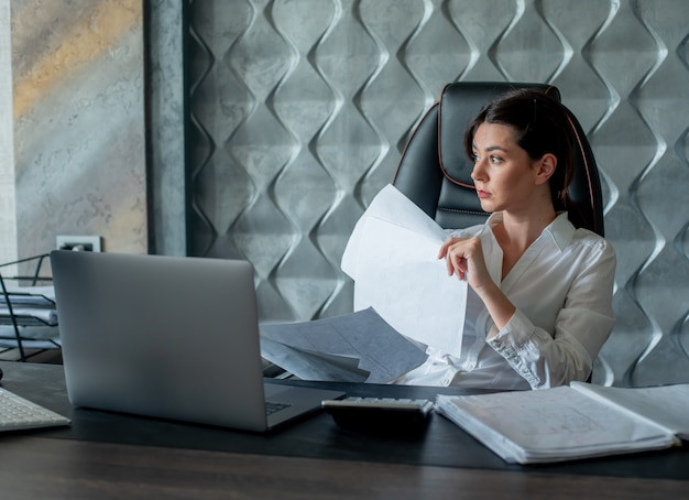 Porträt der jungen büroangestelltenfrau, die am schreibtisch mit dokumenten und laptop-computer sitzt und mit nachdenklichem ausdruck denkt, der im büro arbeitet