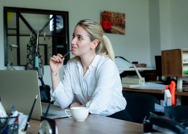 Porträt der jungen büroangestelltenfrau, die am schreibtisch mit laptop-computer sitzt und beiseite denkt mit nachdenklichem ausdruck, der im büro arbeitet