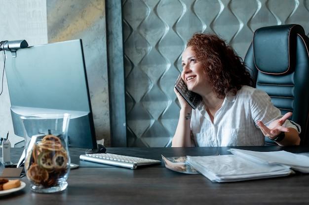 Porträt der jungen büroangestelltenfrau, die am schreibtisch sitzt, der rechner als handy verwendet, das spaß hat, fröhlich im büro zu lächeln