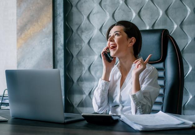 Porträt der jungen büroangestelltenfrau, die am schreibtisch sitzt und auf dem mobiltelefon spricht, das mit dem arbeitsprozess des glücklichen gesichts im büro lächelt