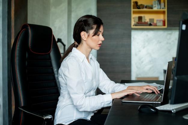 Porträt der jungen büroangestelltenfrau, die am schreibtisch sitzt unter verwendung des laptop-computers, der beschäftigt mit zuversichtlichem ernstem ausdruck auf gesicht arbeitet, das im büro arbeitet