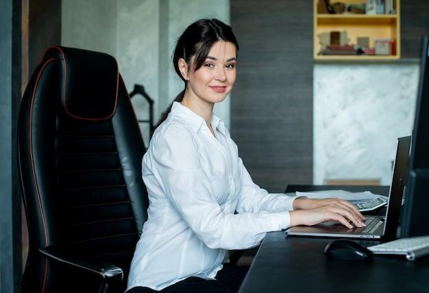 Porträt der jungen büroangestelltenfrau, die am schreibtisch unter verwendung des laptop-computers sitzt, der kamera betrachtet, die fröhlich im büro arbeitet