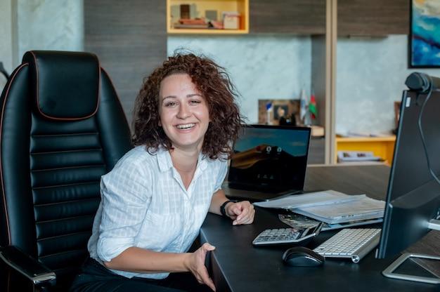 Porträt der jungen büroangestelltenfrau, die am schreibtisch unter verwendung des laptop-computers sitzt, der kamera betrachtet, die fröhlich im hellen büro arbeitet
