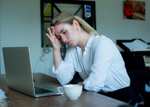 Porträt der jungen büroangestelltenfrau, die am schreibtisch unter verwendung des laptop-computers sitzt, der unwohl berührt kopf berührt, der unter kopfschmerzen leidet, die im büro arbeiten