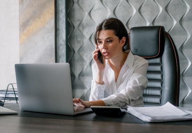 Porträt der jungen büroangestelltenfrau, die am schreibtisch unter verwendung des laptop-computers sitzt, während auf mobiltelefon schaut ängstlicher arbeitsprozess im büro spricht
