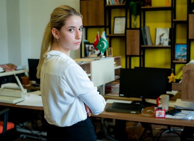 Porträt der jungen büroangestelltenfrau, die seitlich mit verschränkten armen steht und kamera mit ernstem gesicht unzufrieden und sehr besorgt im amt betrachtet