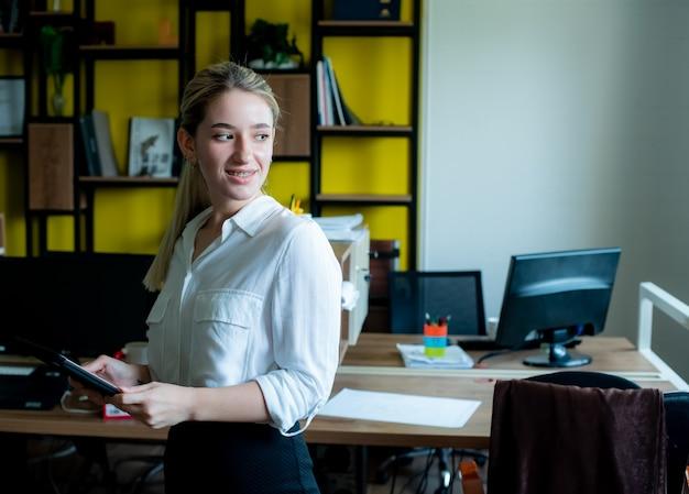Porträt der jungen büroangestelltenfrau, die tablette hält, die beiseite mit lächeln auf gesicht arbeitet, das im büro steht