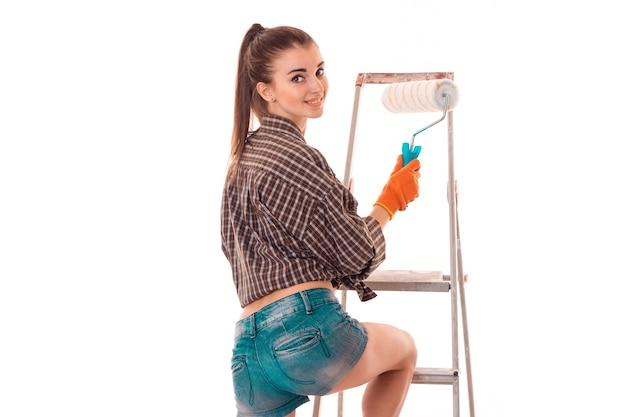 Porträt der jungen charmanten baumeisterin in uniform macht renovierung lokalisiert auf weißer wand