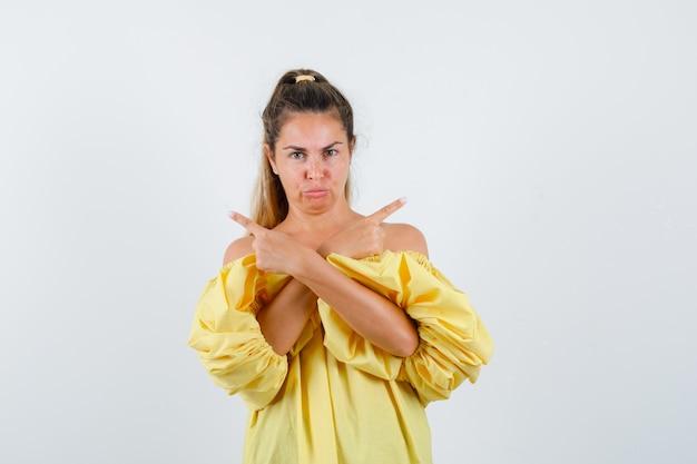 Porträt der jungen dame, die auf beiden seiten im gelben kleid zeigt und zögernde vorderansicht schaut