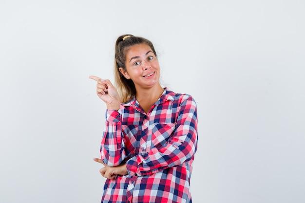Porträt der jungen dame, die auf die linke seite im karierten hemd zeigt und fröhliche vorderansicht schaut