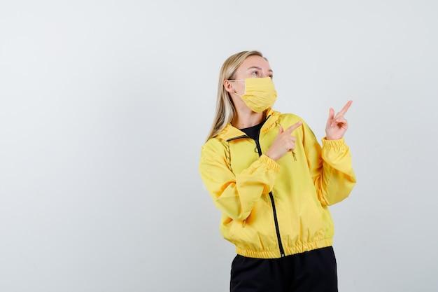 Porträt der jungen dame, die auf die obere rechte ecke im trainingsanzug, in der maske und in der nachdenklichen vorderansicht zeigt