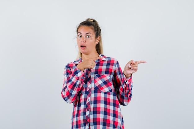 Porträt der jungen dame, die auf die rechte seite im karierten hemd zeigt und ängstliche vorderansicht schaut