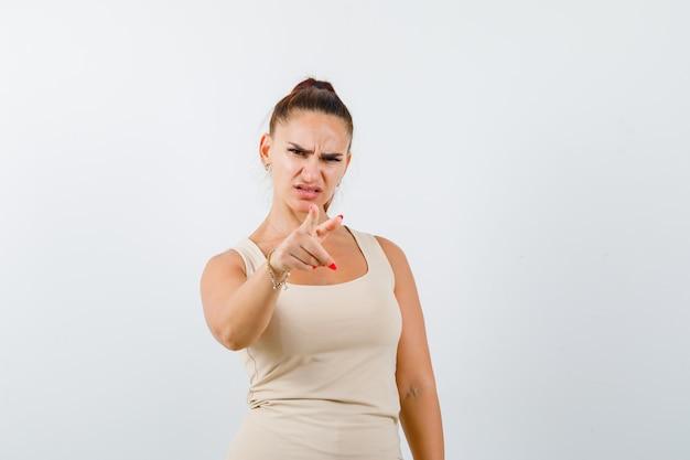 Porträt der jungen dame, die auf kamera im trägershirt zeigt und verärgerte vorderansicht schaut