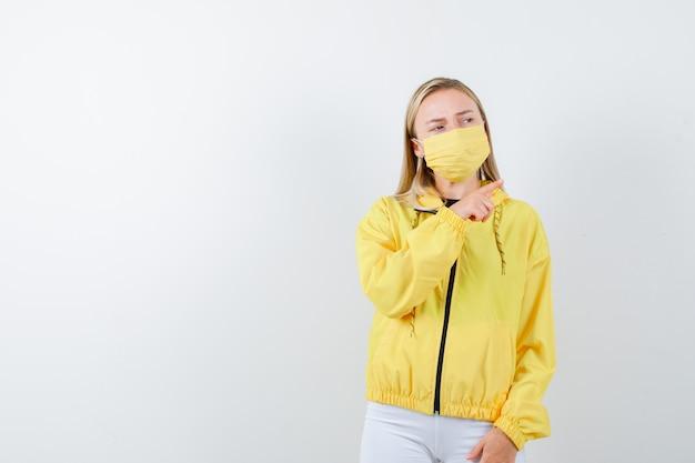 Porträt der jungen dame, die auf obere rechte ecke in jacke, hose, maske zeigt und nachdenkliche vorderansicht schaut