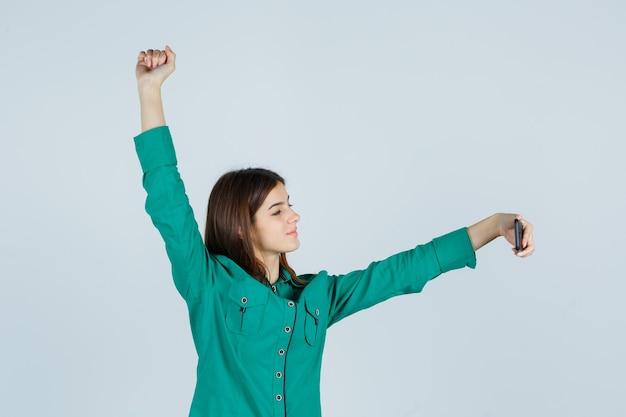 Porträt der jungen dame, die aufwirft, während selfie auf handy in grünem hemd nimmt und glückliche vorderansicht schaut