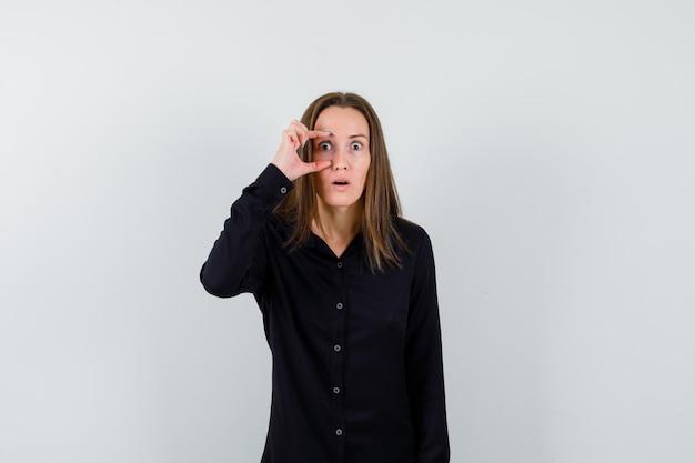 Porträt der jungen dame, die das auge mit den fingern öffnet
