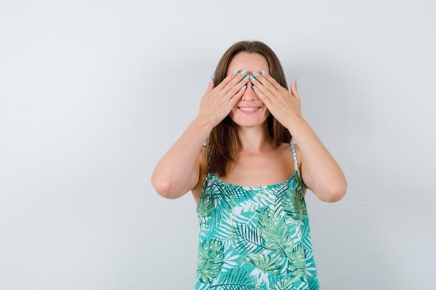 Porträt der jungen dame, die die augen mit den händen in der bluse bedeckt und glückliche vorderansicht schaut
