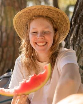 Porträt der jungen dame, die eine scheibe wassermelone hält