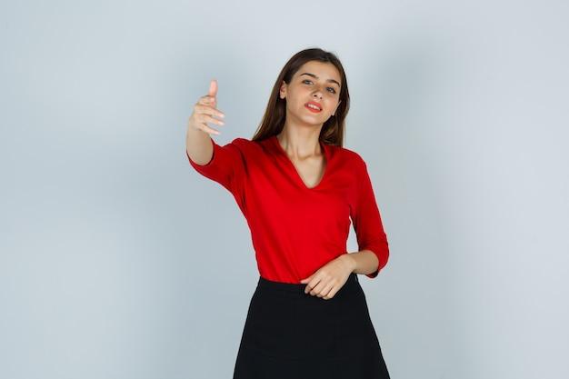 Porträt der jungen dame, die einlädt, in der roten bluse, im rock und in der niedlichen vorderansicht zu kommen