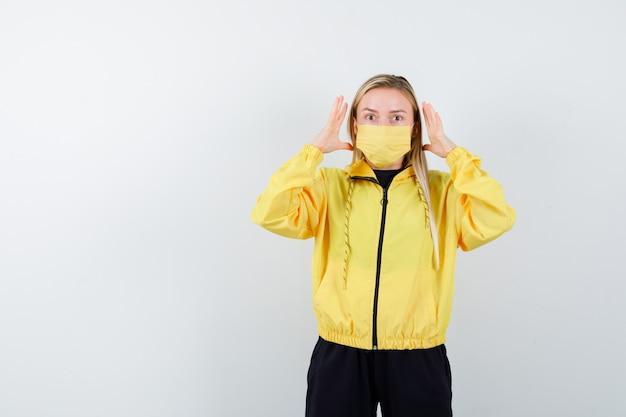 Porträt der jungen dame, die erhobene hände nahe dem kopf im trainingsanzug, in der maske und in der irritierten vorderansicht hält