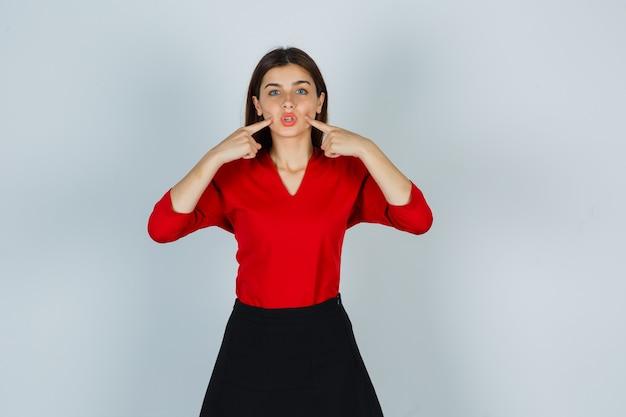 Porträt der jungen dame, die finger auf wangen in roter bluse drückt