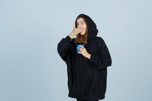 Porträt der jungen dame, die gähnt, während tasse in übergroßem kapuzenpulli, in der hose und in der schläfrigen vorderansicht hält