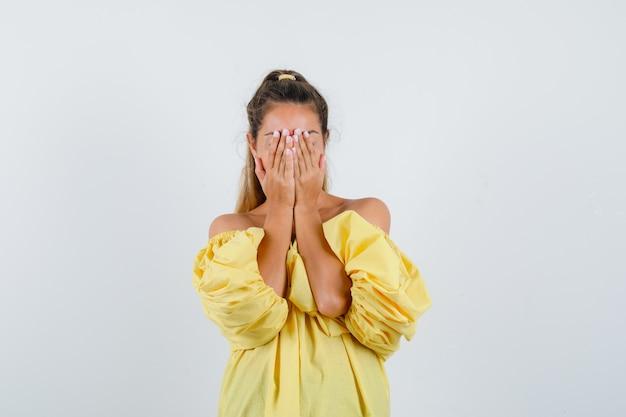 Porträt der jungen dame, die gesicht mit händen im gelben kleid bedeckt und beschämte vorderansicht schaut