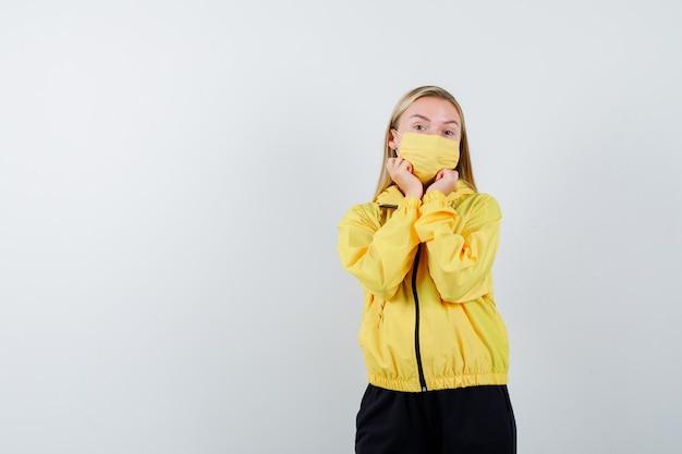 Porträt der jungen dame, die hände unter kinn im trainingsanzug, in der maske und in der vernünftigen vorderansicht hält