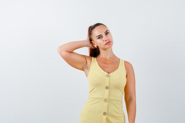 Porträt der jungen dame, die hand hinter kopf im gelben kleid hält und vernünftige vorderansicht schaut