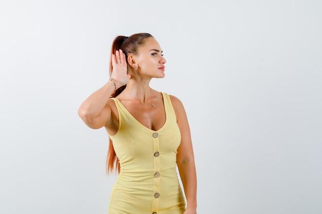 Porträt der jungen dame, die hand hinter ohr im gelben kleid hält und neugierige vorderansicht schaut