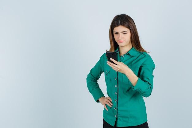 Porträt der jungen dame, die handy im grünen hemd betrachtet und unzufriedene vorderansicht schaut