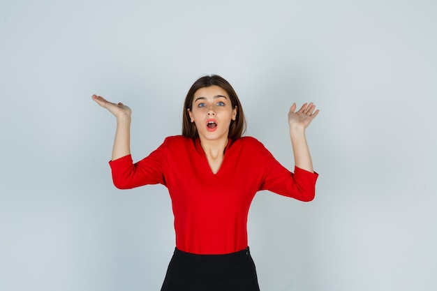 Porträt der jungen dame, die hilflose geste in der roten bluse zeigt