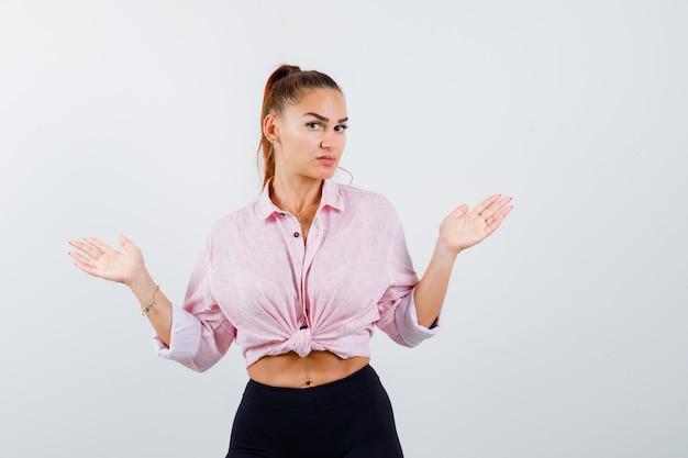 Porträt der jungen dame, die hilflose geste in hemd, hose zeigt und verwirrte vorderansicht schaut