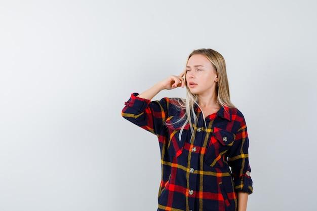 Porträt der jungen dame, die in der denkenden pose im karierten hemd steht und nachdenkliche vorderansicht schaut