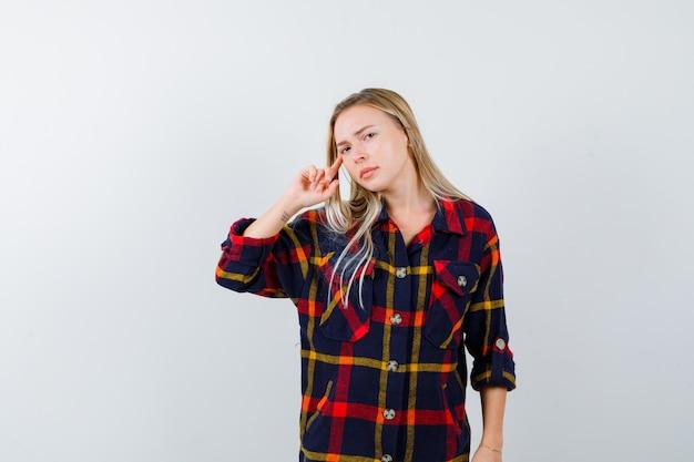 Porträt der jungen dame, die in der denkenden pose im karierten hemd steht und selbstbewusste vorderansicht schaut