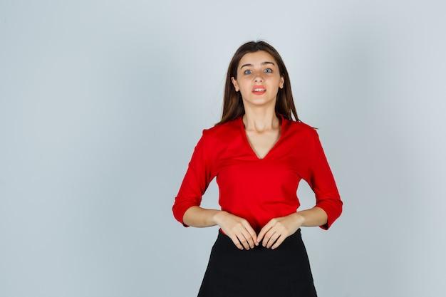 Porträt der jungen dame, die kamera in der roten bluse betrachtet