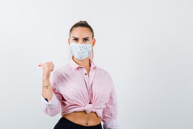 Porträt der jungen dame, die mit daumen in hemd, maske und ernsthafter vorderansicht zurück zeigt
