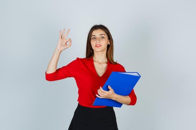 Porträt der jungen dame, die ok geste zeigt, während ordner in roter bluse hält