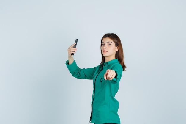 Porträt der jungen dame, die selfie auf handy nimmt, während auf kamera im grünen hemd zeigt und zuversichtlich schaut