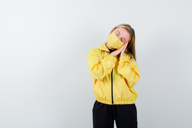 Porträt der jungen dame, die sich auf palmen als kissen im trainingsanzug, in der maske und in der schläfrigen vorderansicht stützt