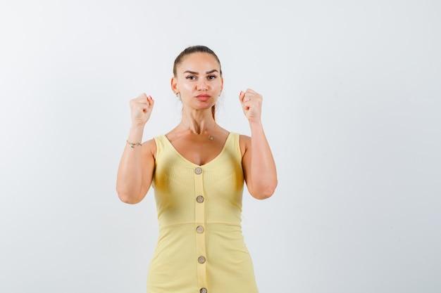 Porträt der jungen dame, die siegergeste im gelben kleid zeigt und selbstbewusste vorderansicht schaut