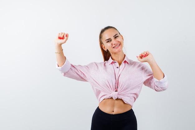 Porträt der jungen dame, die siegergeste in hemd, hose zeigt und glückliche vorderansicht schaut