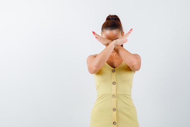 Porträt der jungen dame, die stoppgeste in gelbem kleid zeigt und widerstrebende vorderansicht schaut
