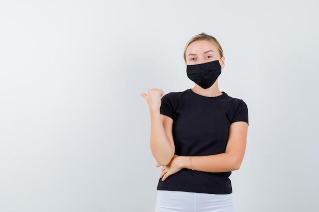 Porträt der jungen dame, die zurück mit daumen in schwarzem t-shirt, maske und selbstbewusster vorderansicht zeigt