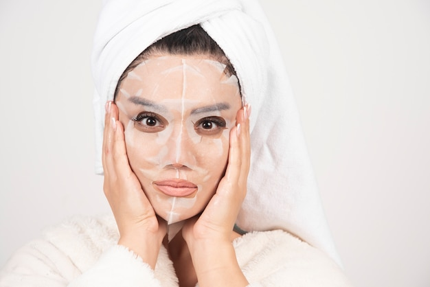 Porträt der jungen dame im bademantel und im handtuch auf kopf, während sie ihr gesicht mit gesichtsmaske berührt.