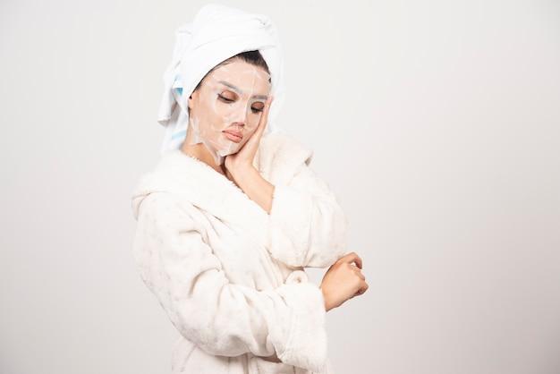 Porträt der jungen dame im bademantel und im handtuch auf kopf, während sie ihr gesicht mit gesichtsmaske berührt