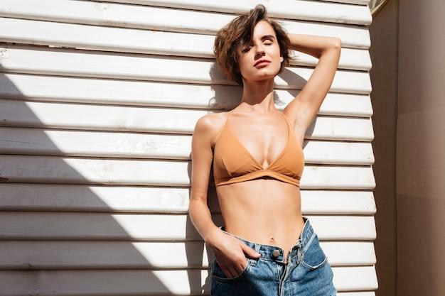 Porträt der jungen dame im bikini und in den jeansshorts, die mit weißen holzbrettern stehen. nettes mädchen im badeanzug und in den kurzen hosen, die aufwerfen