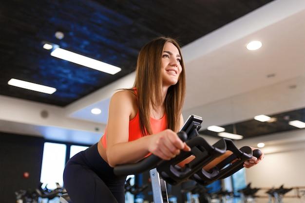 Porträt der jungen dünnen frau im sportwear training auf hometrainer in der turnhalle. sport und wellness lifestyle-konzept