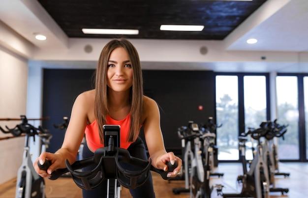 Porträt der jungen dünnen frau im sportwear training auf hometrainer in der turnhalle