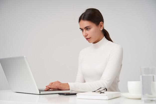 Porträt der jungen dunkelhaarigen geschäftsfrau im weißen gestrickten poloneck, das über weißer wand mit laptop sitzt, hände auf tastatur hält und bildschirm ernsthaft betrachtet